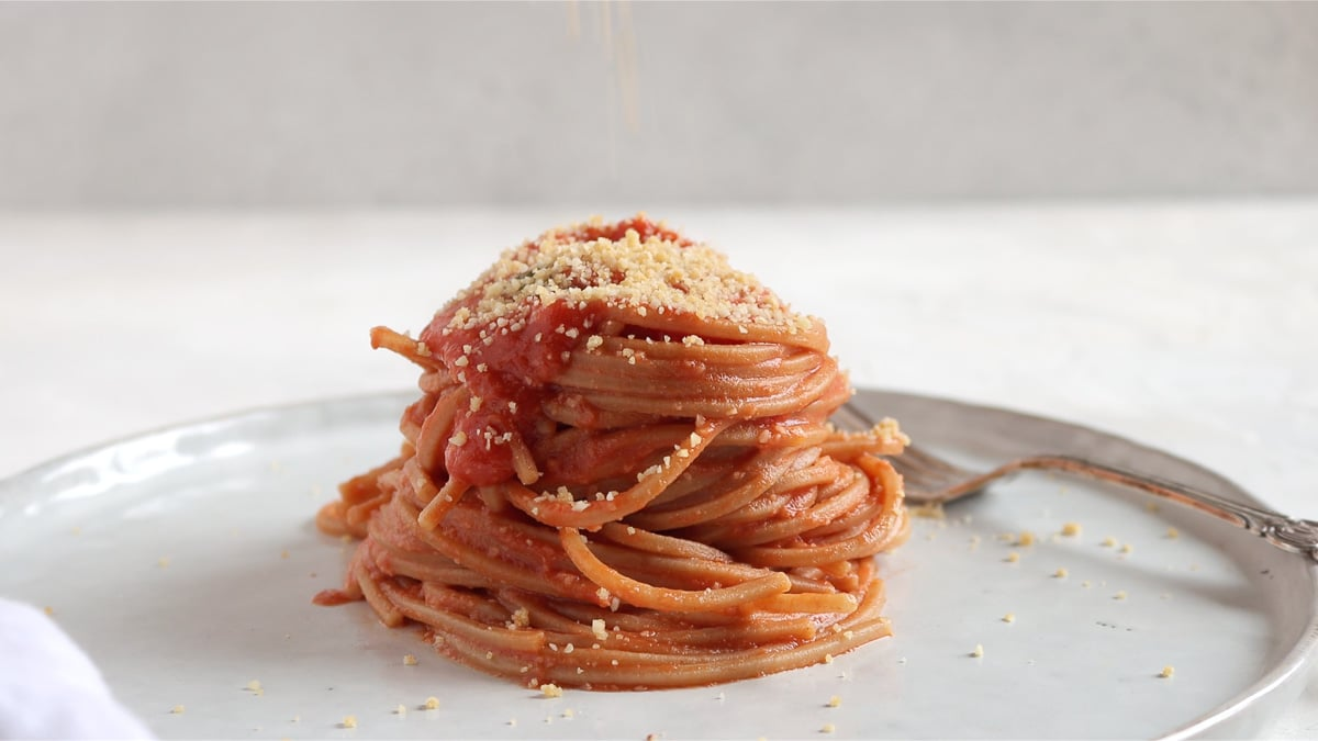 Vegan parmesan on top of spaghetti al pomodoro