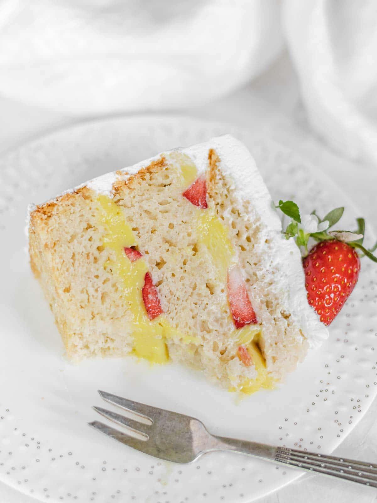 bitten off slice of cake with strawberries