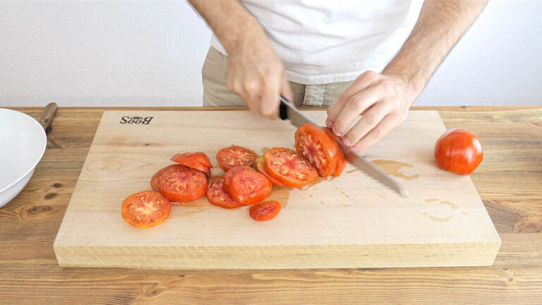 slicing the tomatoes with a serrated knife