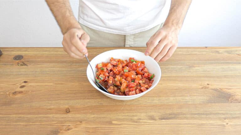 mixing the tomatoes in a bowl with garlic oil and basil