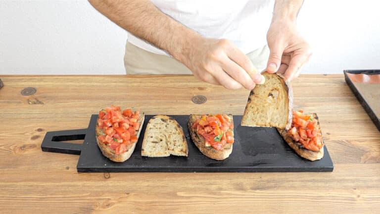 rubbing garlic on the bread to make bruschetta