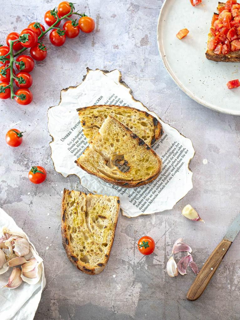 Bruschetta con sale aglio e olio su tavola con pomodorini
