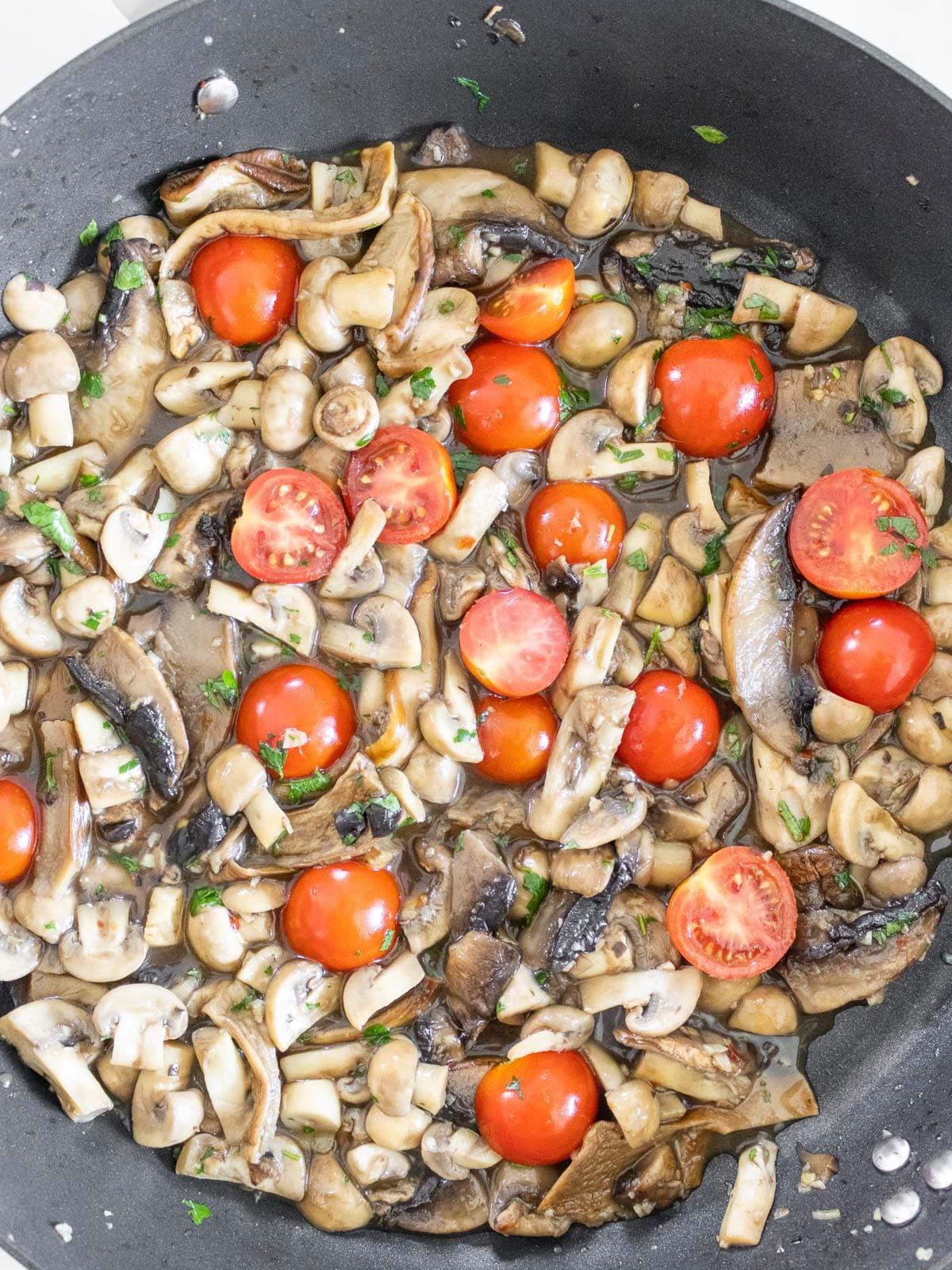 aggiungendo pomodorini e prezzemolo alla salsa di funghi vegana
