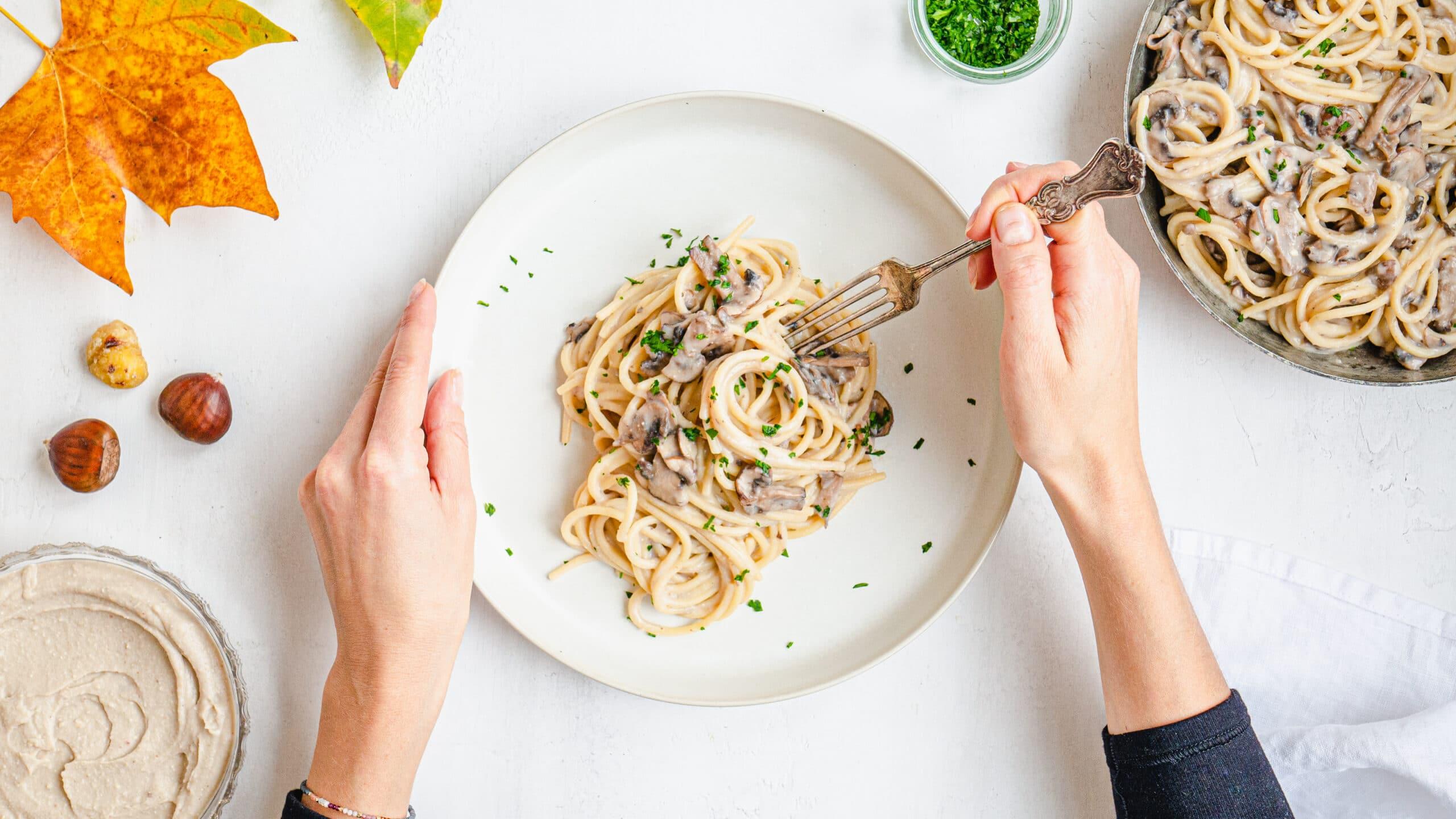 le mani di una ragazza che mangia la pasta con il pesto di castagne