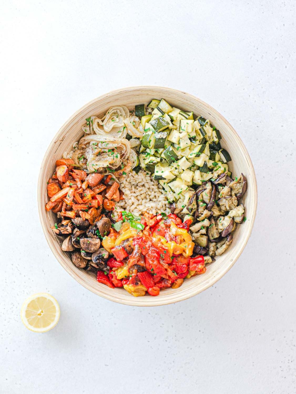 Vegan barley salad in a bowl and a slice of lemon