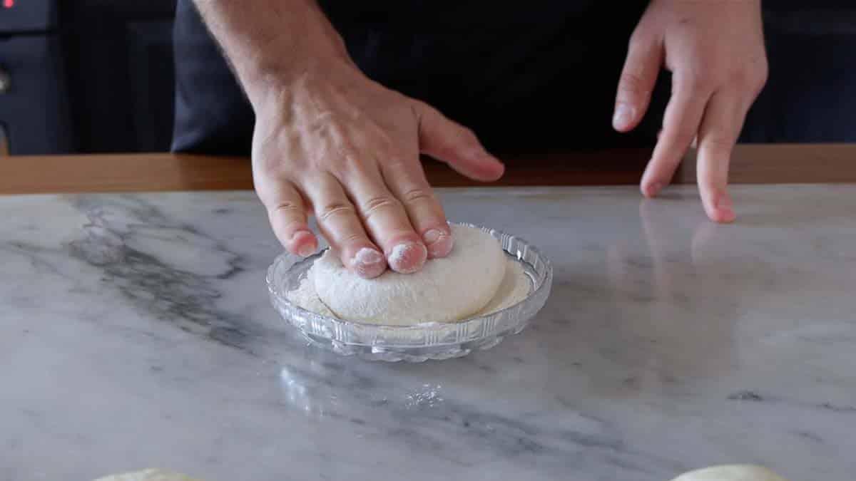 dipping dough ball in flour