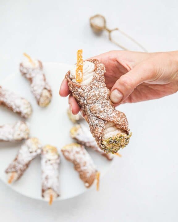 Female hand holding a freshly made cannolo siciliano