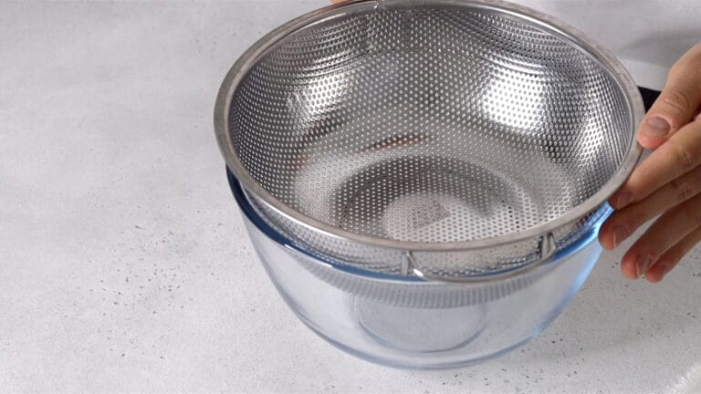 preparing a sieve on top of a large bowl