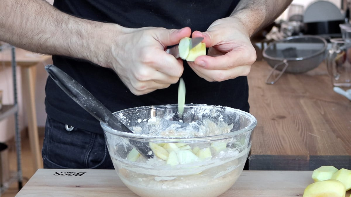 adding apple pieces into cake batter