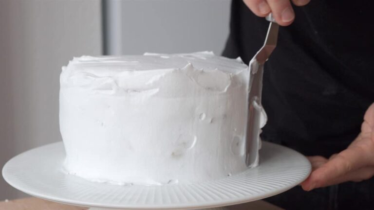 covering the vegano coconut cake with whipped cream