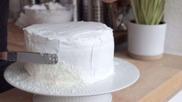 covering the vegan coconut cake with shredded coconut