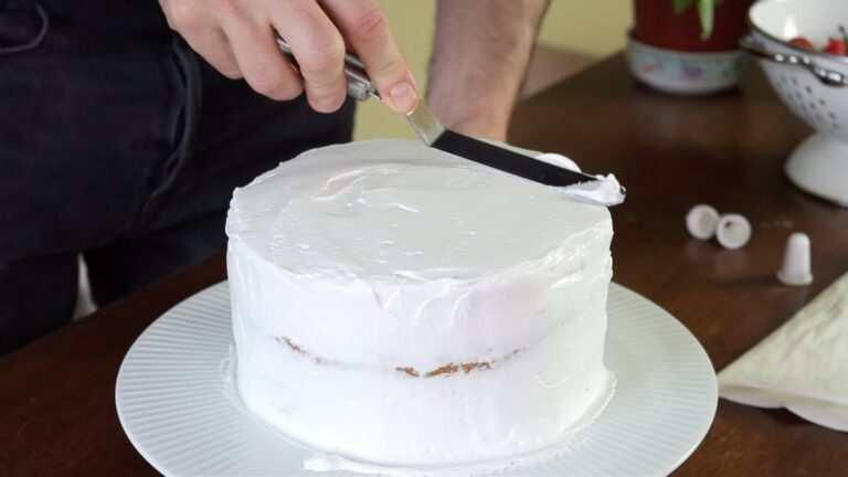 Covering the vegan vanilla cake with whipped cream