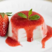 close up dairy free panna cotta with dripping strawberry sauce