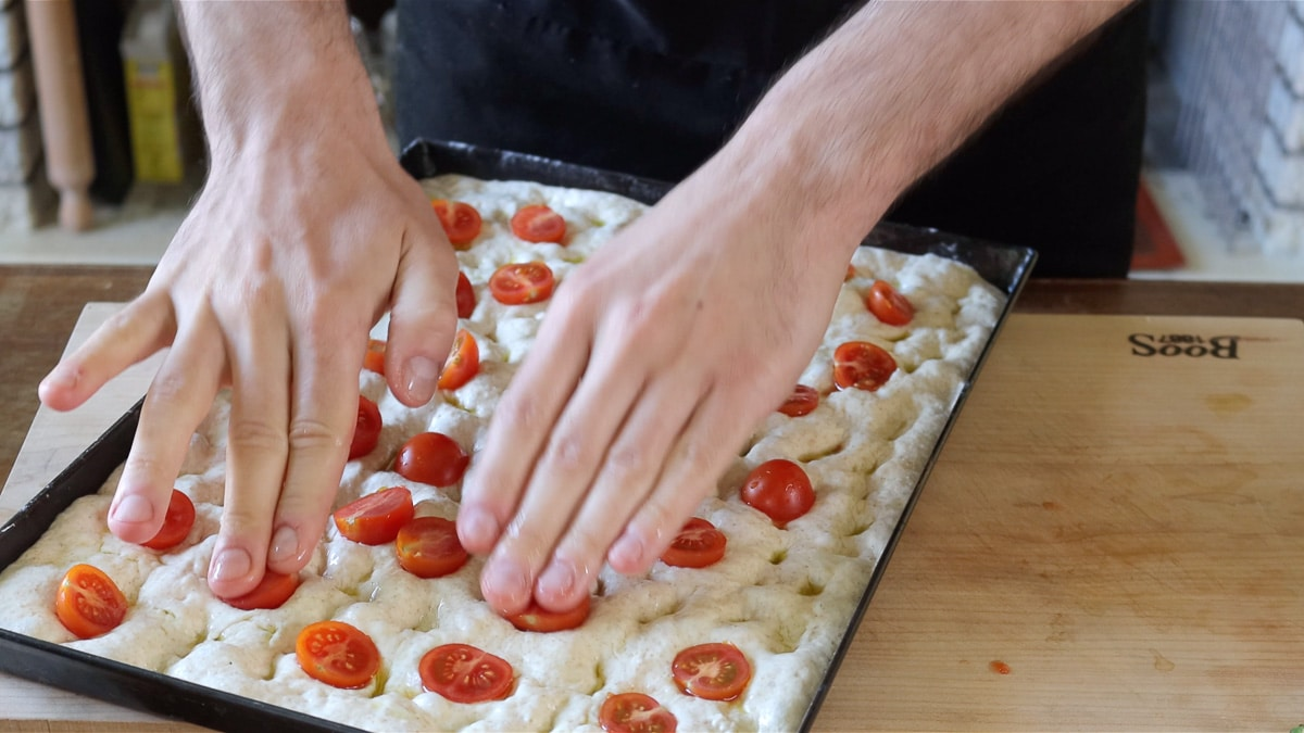 pushing the tomatoes in the dough