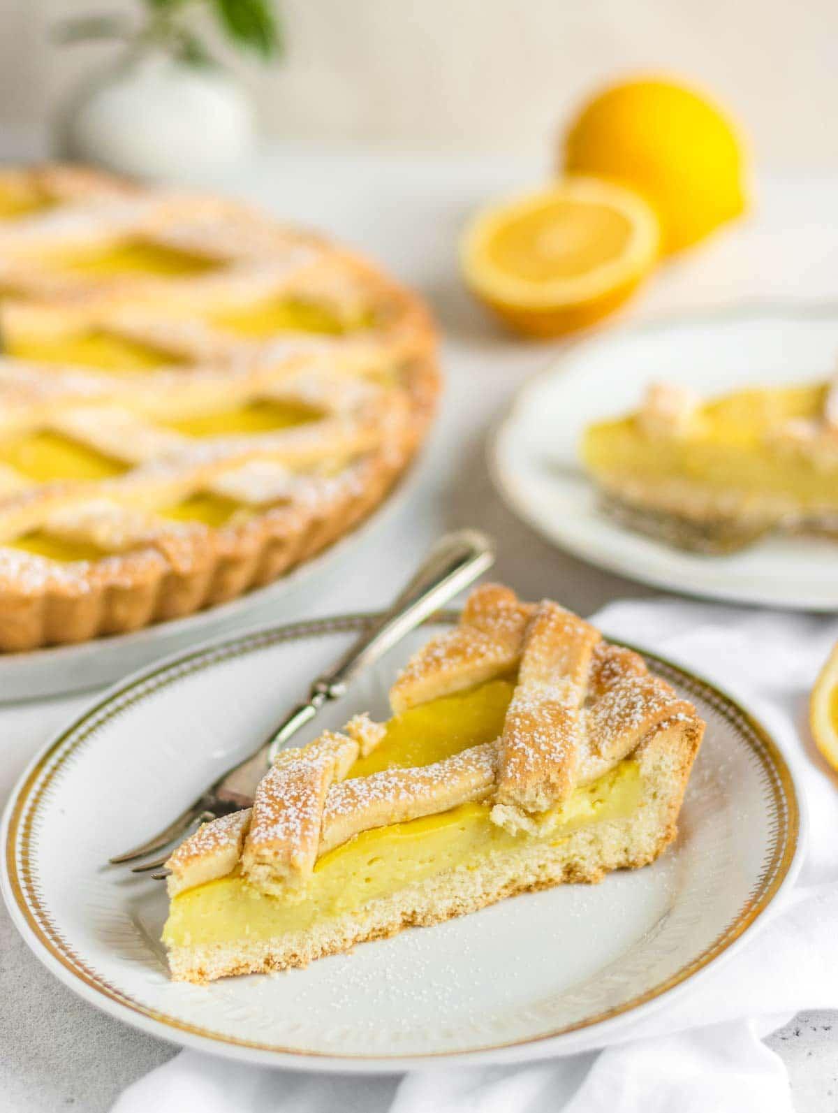 slice of lemon tart on a table with lemons