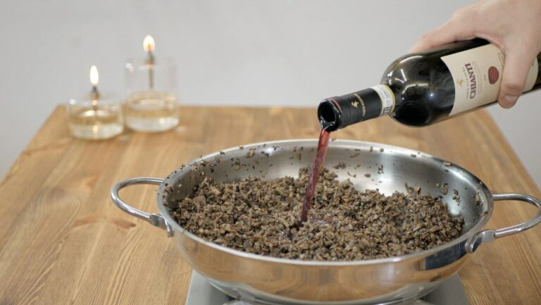 adding the red wine to the pan