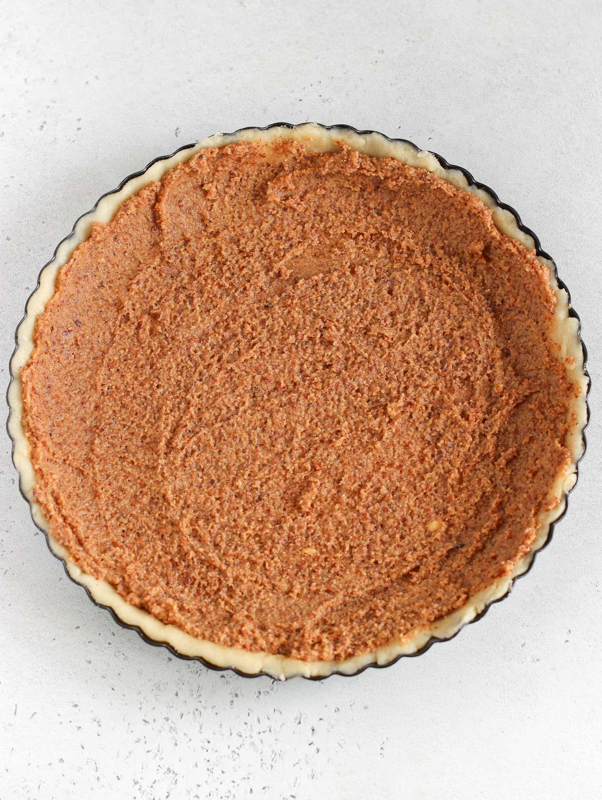 Spreading the frangipane on the pie crust