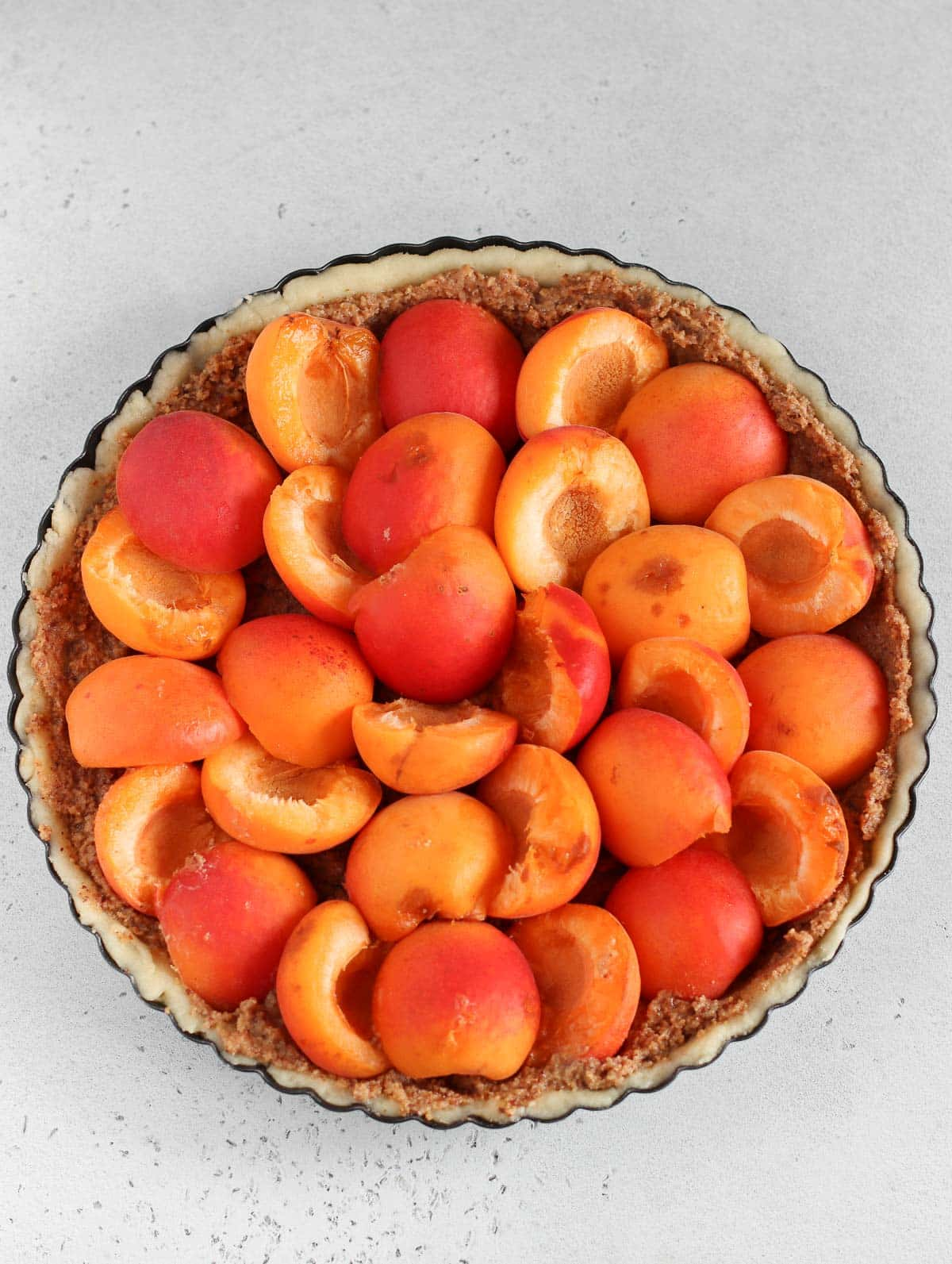 putting the apricots on the apricot tart