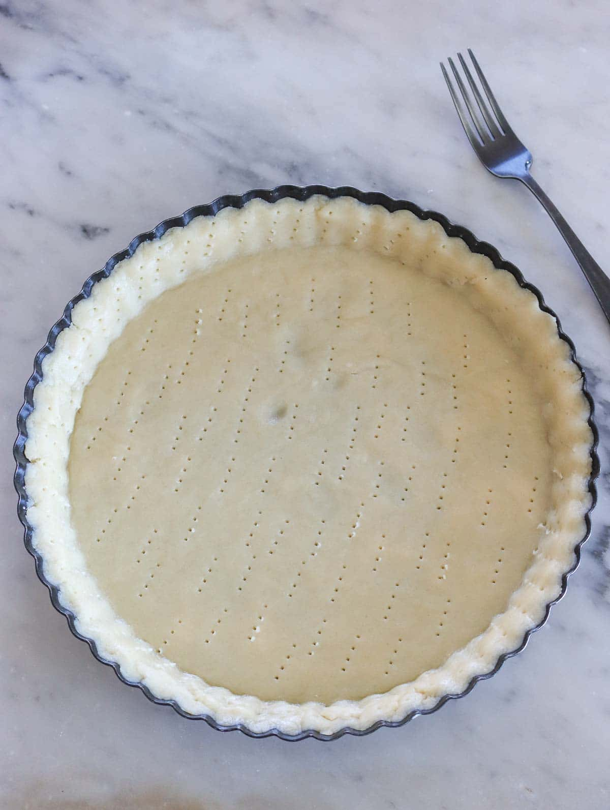 pie crust in pie dish with fork holes