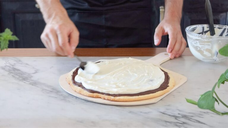 spreading the cream cheese on top of the fruit pizza