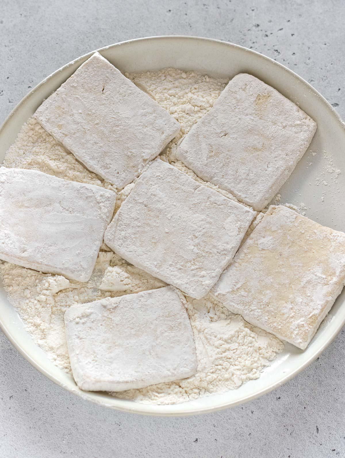 ricoprire il tofu con la farina su un piatto