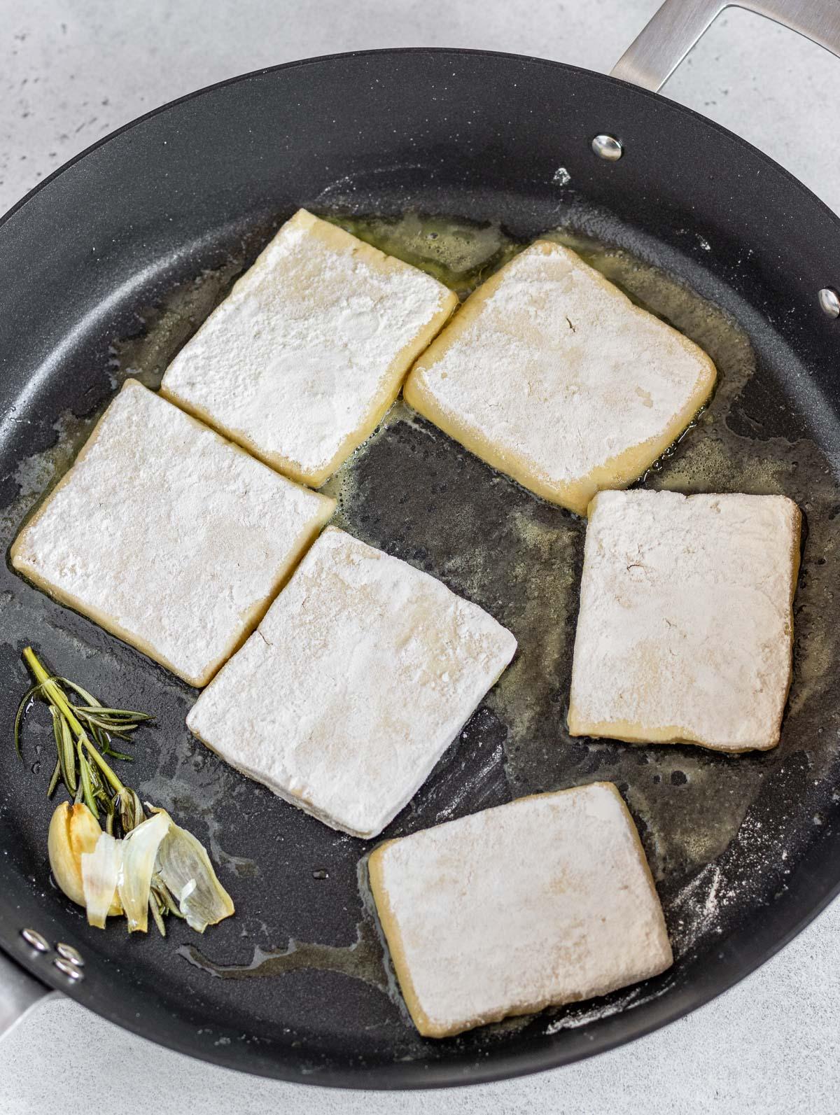 friggere le fette di tofu in una padella con olio e aglio