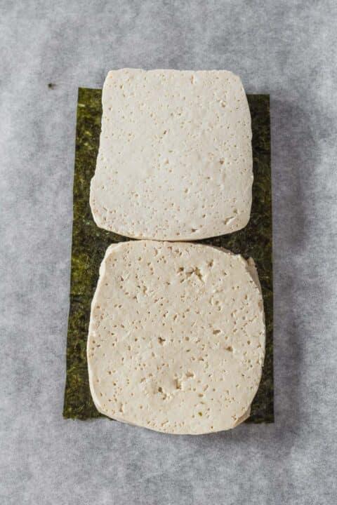 due pezzi di tofu sopra un pezzo di foglio di nori