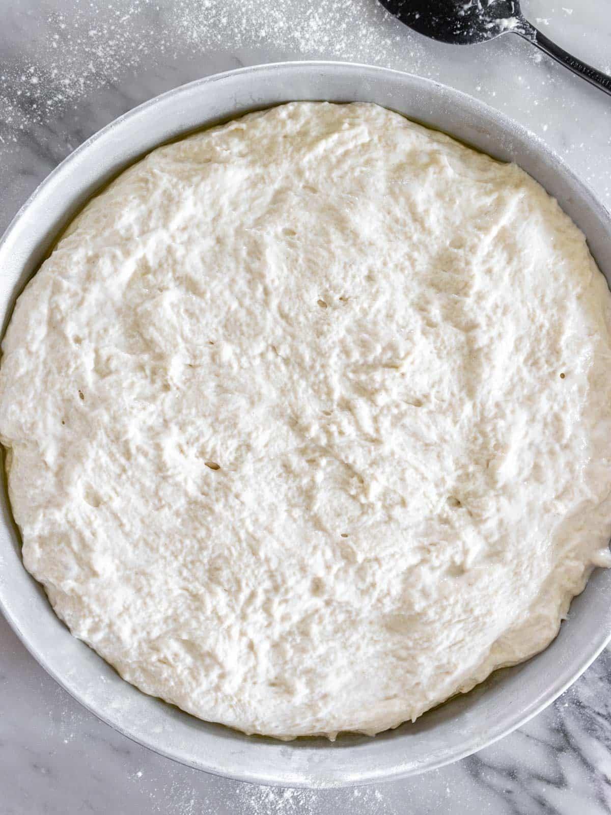 focaccia no knead in a baking tray