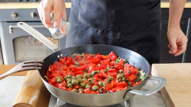 adding olives, capers and tomatoes to the pan
