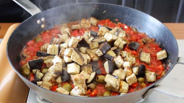 adding baked eggplants to the pan