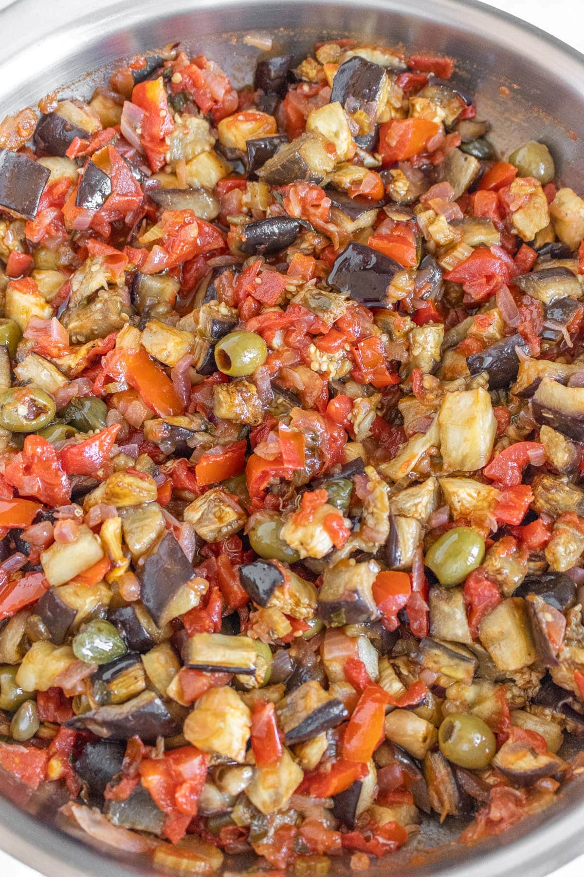 adding the baked eggplant to the caponata sauce
