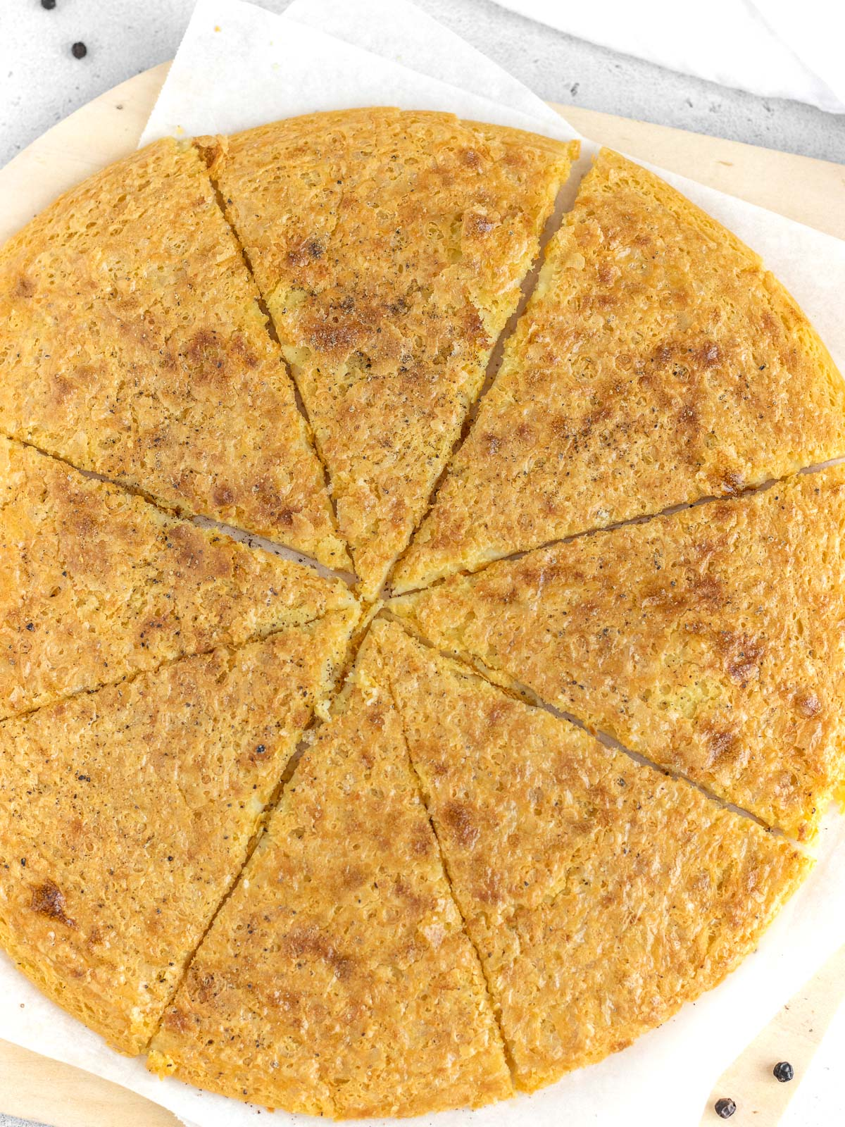 just baked farinata cut and sprinkled with pepper