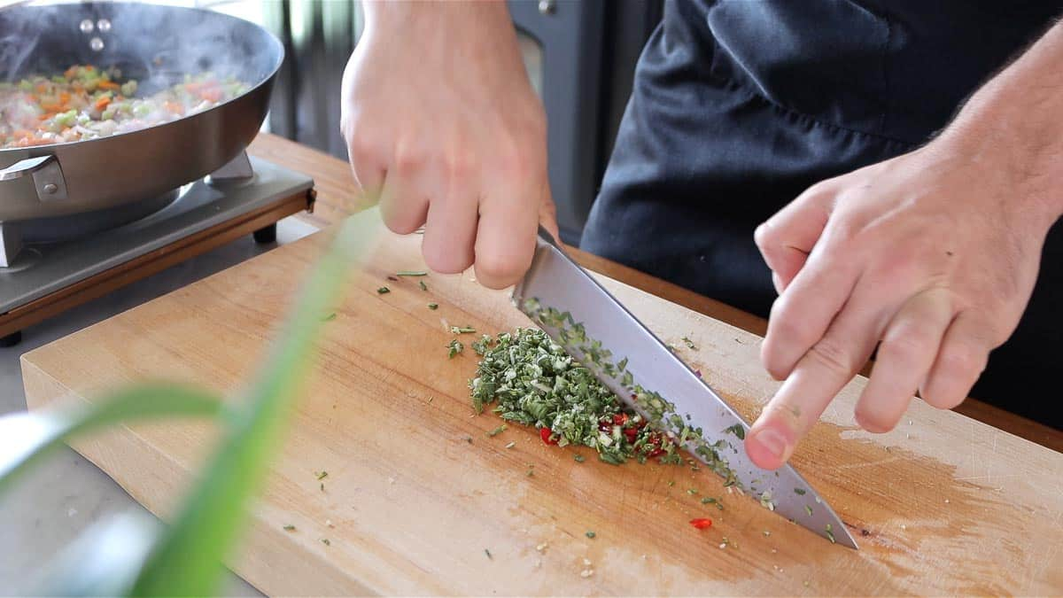 chopping sage, rosemary, garlic and chili peppers