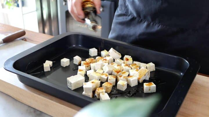 seasoning tofu cubes with soy sauce, oil and salt